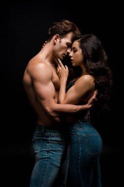 beautiful seductive girlfriend and boyfriend hugging, isolated on black