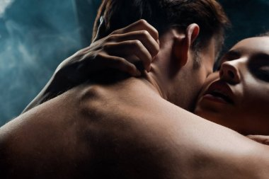 passionate couple hugging in black room with smoke