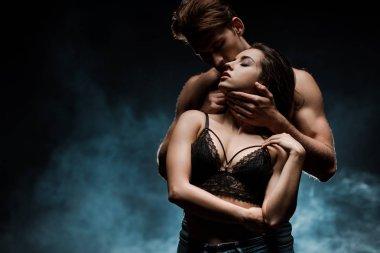 sensual couple hugging in black room with smoke