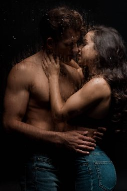beautiful passionate couple hugging and kissing behind wet glass