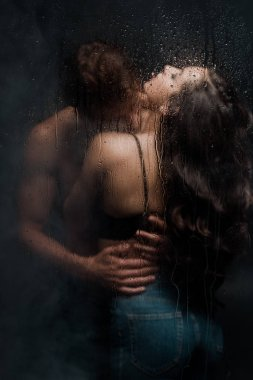 sexy couple hugging and kissing behind wet glass