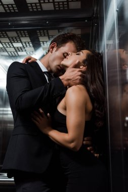 handsome man hugging and kissing beautiful sexy woman in lift