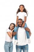 šťastný africký americký žena opírá o rameno manžela piggybacking rozkošný dcera izolované na bílém