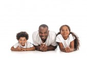 happy african american father, son and daughter smiling at camera while lying on white background
