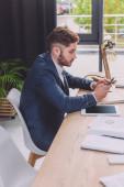 fiatal üzletember okostelefon közelében digitális tabletta tárgyalóteremben