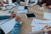 Fotografia vista ritagliata di uomini daffari seduti alla scrivania vicino a dispositivi digitali, quaderni e documenti in sala riunioni