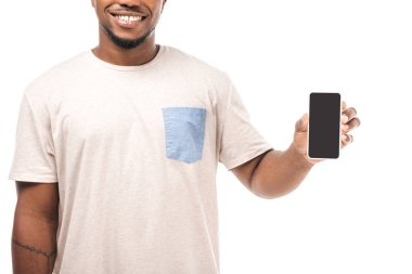 Partial view of smiling african american man holding smartphone with blank screen isolated on white stock vector