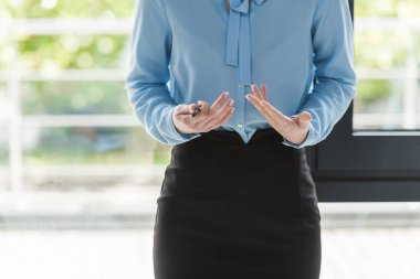 cropped view of businesswoman in formal wear showing explain gesture during business meeting