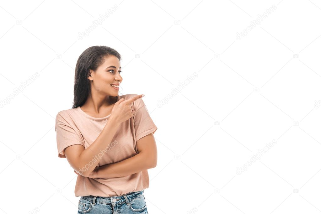 Smiling african american woman looking away and pointing with finger isolated on white stock vector