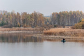 LVIV, UKRAJINA - 23. října 2019: pohled zezadu na rybáře držícího rybářskou prut při sedění na člunu a rybaření v jezeře