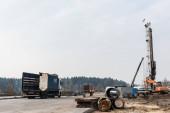 LVIV, UKRAJINA - 23. října 2019: nákladní automobil u osobních automobilů a jeřáb proti obloze