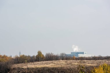 LVIV, UKRAINE - OCTOBER 23, 2019: smoke near factory with cersanit lettering and green trees against sky stock vector