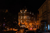 LVIV, UKRAINE - OCTOBER 23, 2019: buildings with lighting near road with cars at night