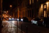 LVIV, UKRAINE - 23. OKTOBER 2019: Beleuchtung von Straßen in der Nähe von Gebäuden mit kyrillischen Schriftzügen in der Nacht