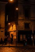 LVIV, UKRAINE - 23. OKTOBER 2019: Straßenlaternen in der Nähe von Menschen auf dunklen Straßen