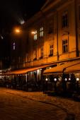 dunkle Straße und Silhouette von Menschen, die in einem Café mit Terrasse sitzen