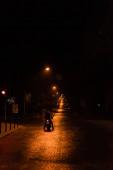 LVIV, UKRAINE - 23. OKTOBER 2019: Silhouette eines Mannes mit Helm, der nachts auf der Straße Roller fährt