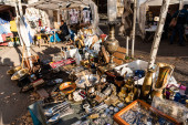 LVIV, UKRAINE - OCTOBER 23, 2019: vendor on flea market near stall with vintage cutlery, souvenirs and jewelry