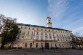 LVIV, UKRAINE - Október 23, 2019: homlokzata lviv városháza torony és az emberek sétálnak az utcán