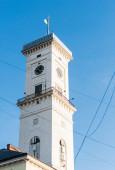 lvovská radniční věž s kulatými hodinami proti modré obloze