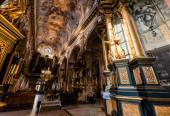 LVIV, UKRAJINA - 23. října 2019: interiér karmelitánského kostela s malbami na stropě a stěnách a zlacenými sloupy