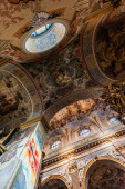LVIV, UKRAINE - OCTOBER 23, 2019: bottom view of arch and ceiling with paintings in carmelite church