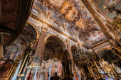 LVIV, UKRAINE - OCTOBER 23, 2019: interior of carmelite church with beautiful paintings on ceiling and gilded chandeliers