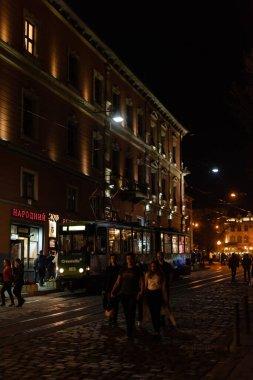 LVIV, UKRAINE - OCTOBER 23, 2019: tram near people walking on street in evening stock vector