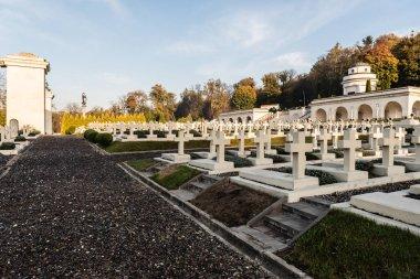 LVIV, UKRAINE - OCTOBER 23, 2019: rows of polish graves with crosses near gravel road in lychakiv cemetery in lviv, ukraine stock vector