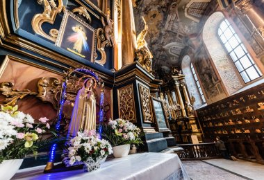 LVIV, UKRAINE - OCTOBER 23, 2019: altar with our lady statue, decorated with natural flowers in carmelite church stock vector