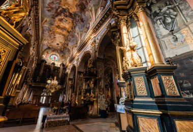 LVIV, UKRAINE - OCTOBER 23, 2019: interior of carmelite church with paintings on ceiling and walls, and gilded columns stock vector