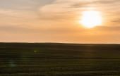 malerische Landschaft mit gemähtem Feld bei Sonnenuntergang in der Ukraine