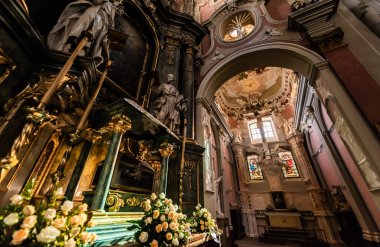 LVIV, UKRAINE - OCTOBER 23, 2019: low angle view of carmelite church interior decorated with gilding, sculptures and natural flowers stock vector