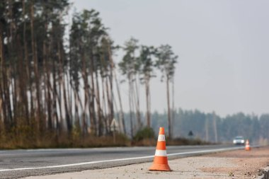 roadwork cones near highway with car moving with lighting headlamps in ukraine