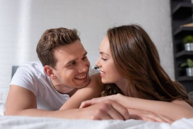Selective focus of happy young couple smiling while looking at each other in bedroom stock vector