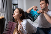 Photo handsome man holding magazine near displeased girl feeling hot at home