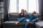 Photo woman sitting on sofa near man holding remote controller from air conditioner while feeling hot