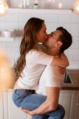 selektivní zaměření muže se zavřenýma očima líbání a držení v náručí atraktivní dívka