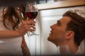 nő kezében pohár vörösbor közelében jóképű férfi