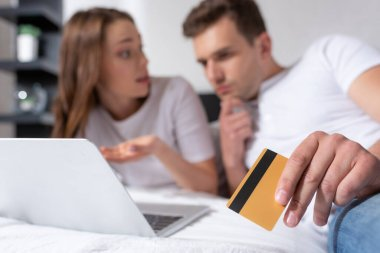 Selective focus of pensive man holding credit card near girl and laptop stock vector