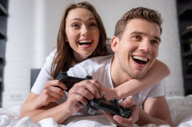 KYIV, UKRAINE - MAY 15, 2020: excited woman and man playing video game in bedroom stock vector