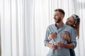 happy young woman hugging smiling boyfriend at home