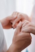 cropped view of woman with engagement ring on finger holding hands with man