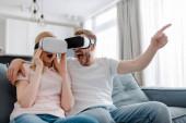 Aufgeregter Mann zeigt mit Finger auf Mädchen in Virtual-Reality-Headset zu Hause