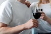 oříznutý pohled na muže a ženu držící sklenice s červeným vínem
