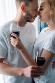 Seitenansicht von fröhlichen Mann und Frau mit Gläsern mit Rotwein
