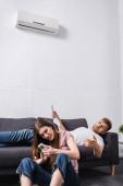 Fotografie junges Paar mit Fernbedienung und Zeitung leidet unter Hitze, während es mit defekter Klimaanlage zu Hause sitzt
