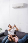 worried couple with remote controller suffering from heat at home with broken air conditioner