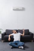 Erschöpfter Mann fühlt sich bei Sommerhitze mit defekter Klimaanlage zu Hause unwohl