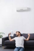 szomorú fiatalember szenved hő használata közben újság kézi ventilátor otthon törött légkondicionáló